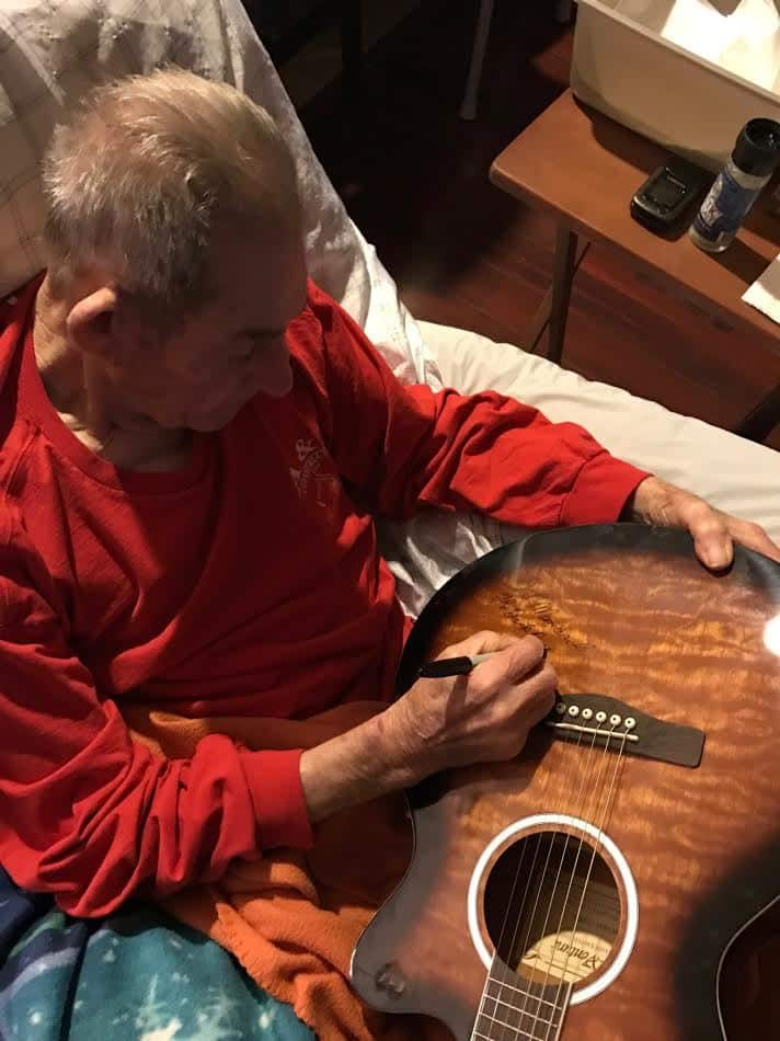 Mr. D.L. Menard signing the CMR raffle guitar